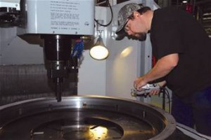 A skilled machinist monitors the cut on a vertical turning centre.